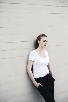 Portrait of cool young woman leaning against wall - UUF12325