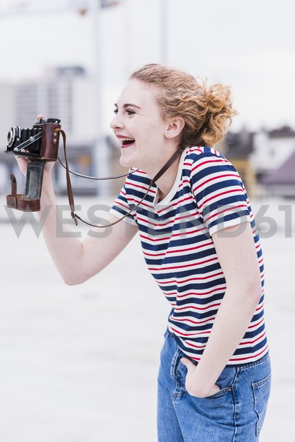 Portrait of laughing young woman with vintage camera - UUF12331