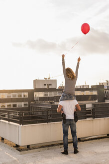 Back view of young couple on roof terrace at sunset - UUF12343