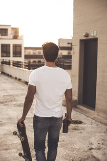 Back view of young man with skateboard and beer bottle on roof terrace at evening twilight - UUF12346