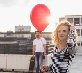 Portrait of smiling young wo man with red balloon on roof terrace at sunset - UUF12349