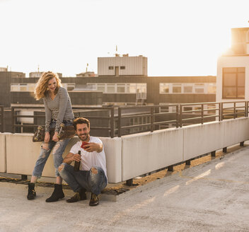 Young couple relaxing on roof terrace at sunset taking selfie with cell phone - UUF12352