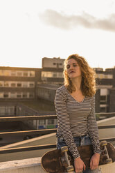 Portrait of young woman with skateboard enjoying sunset on roof terrace - UUF12355