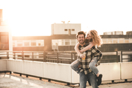 Portrait of young man giving his  girlfriend a piggyback ride on roof terrace at sunset - UUF12361