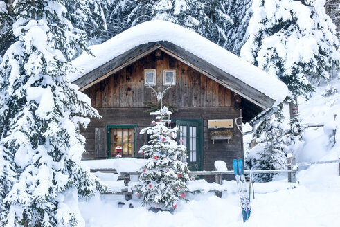 Austria, Altenmarkt-Zauchensee, Christmas tree at wooden house in snow - HHF05527