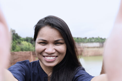 Thailand, Chiang Mai, self portrait of smiling young woman - IGGF00197