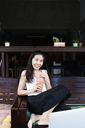 Portrait of smiling woman sitting on terrace bench drinking a smoothie - IGGF00207
