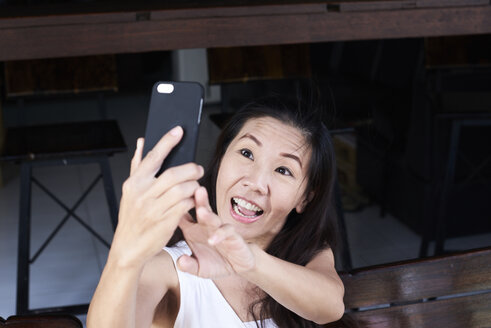 Happy woman taking a selfie with smartphone - IGGF00213