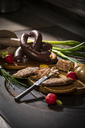 Liver sausage, blood sausage,  spring onion, red radish, chives, mustard, bread on chopping board, hotplate - MAEF12460