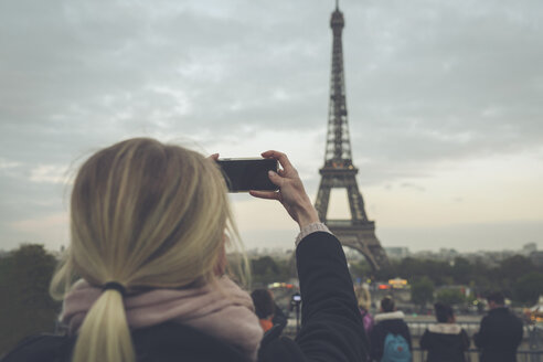 France, Paris, Eiffel Tower, woman photographing with smartphone - CHPF00454