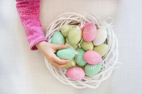 Girl's hand taking coloured Easter egg - LVF06435