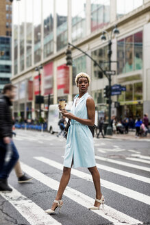 USA, New York, young blonde african-american woman with cup of coffee and smart phone crossing street - MAUF01238