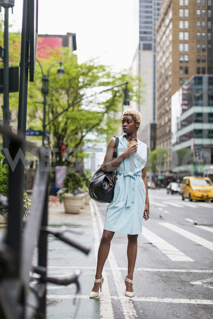 USA, New York, young blonde african-american woman with coffee mug and smart phone - MAUF01241