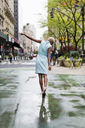 USA, New York, young blonde african-american woman walking in puddle - MAUF01244