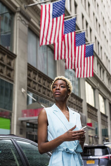 USA, New York, young blonde african-american woman with smartphone - MAUF01250