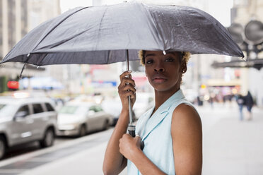 USA, New York, Portrait of young blonde african-american woman with umbrella - MAUF01256