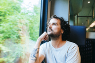 Man traveling by train looking out of window - KIJF01715