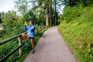Germany, Triberg, Woman taking a photo with mobile phone on path - KIJF01721