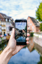 France, Colmar, close-up of a hand of a man taking a picture with his smartphone - KIJF01724