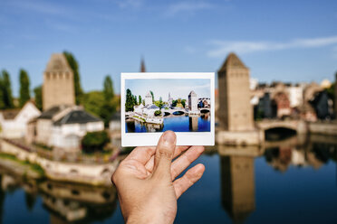France, Strasbourg,hand holding instant photography of the Strasbourg towers with the same real landscape in the background - KIJF01727