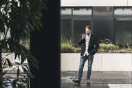 Young businessman using smartphone outside the office - UUF12379