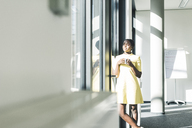 Businesswoman looking out of the window in office - UUF12382