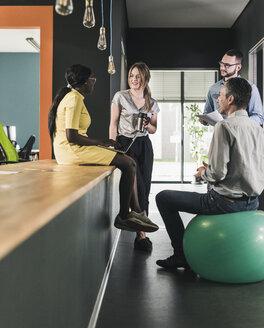 Business people having an informal meeting in office - UUF12412