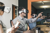 Colleagues wearing VR glasses in office - UUF12415