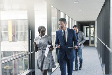 Business people walking on office floor - UUF12424