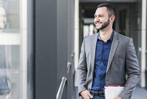 Portrait of smiling businessman on office floor - UUF12427