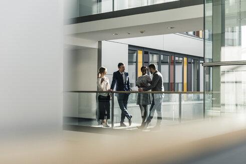 Business people talking on office floor - UUF12433