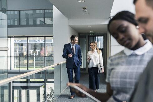 Business people talking on office floor - UUF12436