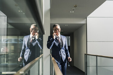 Smiling businessman talking on cell phone on office floor - UUF12439