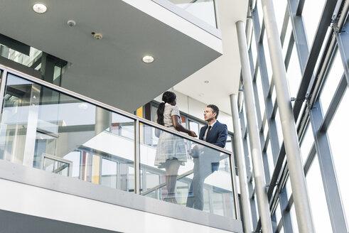 Businessman and woman talking on office floor - UUF12445