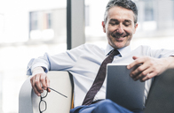 Smiling businessman sitting in lounge with tablet - UUF12451