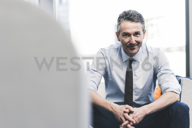 Portrait of smiling businessman sitting in lounge - UUF12454