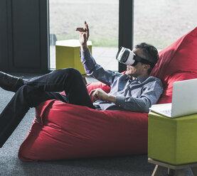 Man sitting in beanbag wearing VR glasses - UUF12466