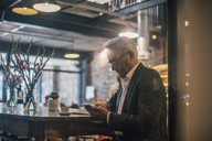 Senior businessman sitting in cafe, using smartphone - GUSF00175