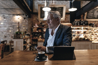 Senior businessman sitting in cafe, using digital tablet, daydreaming - GUSF00181