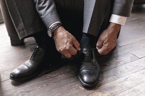 Businessman putting on shoes, tying shoelace - GUSF00187
