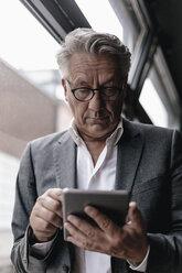 Businessman leaning on window, using digital tablet - GUSF00190
