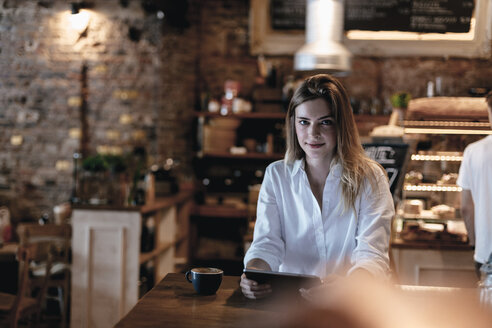 Smiling blond woman sitting in cafe, using tablet - GUSF00202