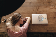 Young woman looking at shopping cart on laptop, shopping online - GUSF00208
