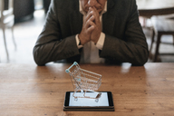 Senior businessman looking at shopping cart on digital tablet - GUSF00241