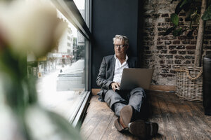 Businessman sitting on floor next to window, using laptop - GUSF00244