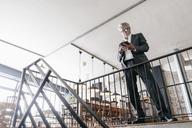 Senior businessmans standing at railing, using digital tablet - GUSF00247