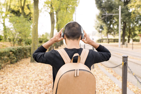 Young man with headphones and backpack outdoors - FMOF00327