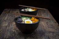 Ramen with noodles, egg, hokkaido pumpkin, mung sprout, shitake mushroom in bowl, chopsticks - LVF06451