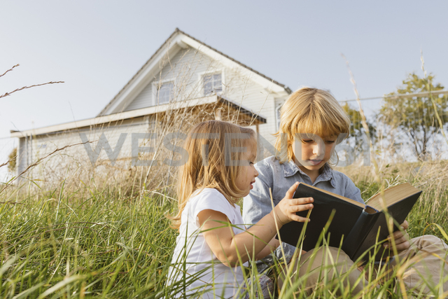 Brother and his little sister sitting on a meadow reading a book - KMKF00067