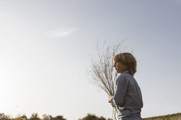 Boy with twigs against sky - KMKF00070